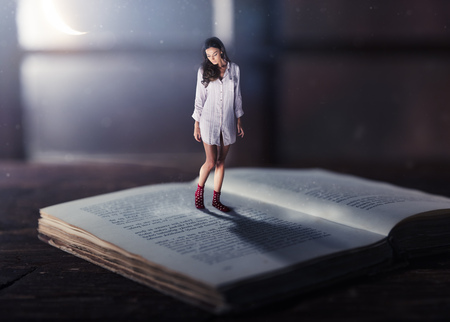 Good night concept with shrinked young woman reading book. Miniature unreal dreamy scene with moonlight Stock Photo