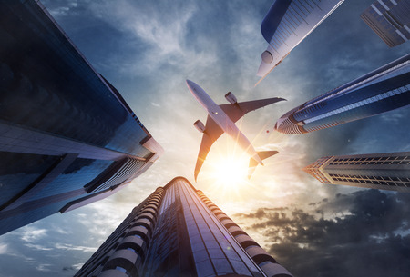 Commercial airplane flying above skyscrapers. Concept of modern technologies, business and fast travel. 写真素材
