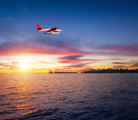 Beautiful sunset on Maldives resort with commercial seaplane flying over water villas and tropical island Stock Photo