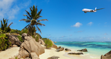 Beautiful panoramic view of beach in Seychelles with commercial airplane, island La Digue, Anse Source dArgent.