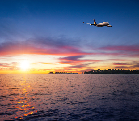 Beautiful sunset on Maldives resort with commercial airplane flying over water villas and tropical island Фото со стока