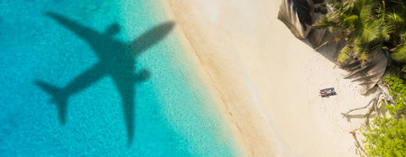 Concept of airplane travel to exotic destination with shadow of commercial airplane flying above beautiful tropical beach.