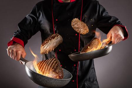 Primer plano de chef tirando filetes de ternera al aire, llamas de fuego alrededor. Concepto de preparación de alimentos Foto de archivo