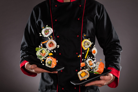 Closeup of master chef holding plates with flying sushi pieces. Concept of asian food Imagens