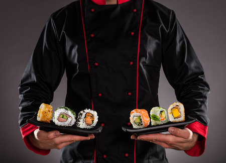 Closeup of master chef holding plates with sushi pieces. Concept of asian food
