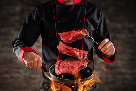 Closeup of chef throwing raw beef steaks into the air. Concept of food preparation, grill and barbecue Foto de archivo