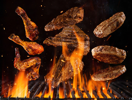 Flying beef steaks, hamburgers and chicken pieces above burning grill grid, isolated on black backround. Barbecue and grill concept