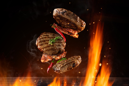 Flying beef hamburgers pieces above burning grill grid, isolated on black backround. Barbecue and grill concept Stok Fotoğraf