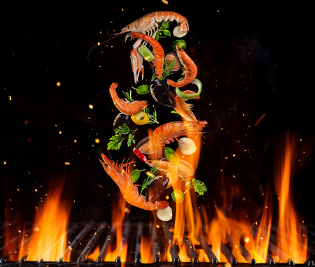 Flying sea fruit and vegetable pieces above burning grill grid, isolated on black backround. Barbecue and grill concept