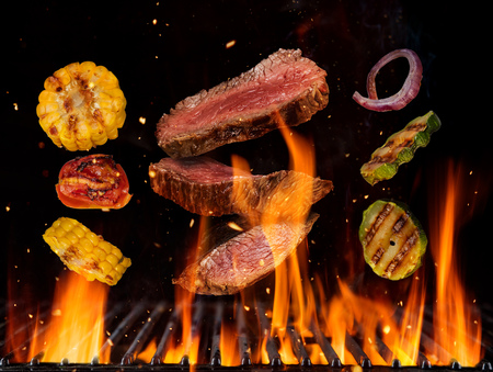 Flying raw beef steaks and vegetable pieces above burning grill grid, isolated on black backround. Barbecue and grill concept