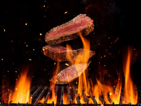 Flying raw beef steaks pieces above burning grill grid, isolated on black backround. Barbecue and grill concept Stock Photo