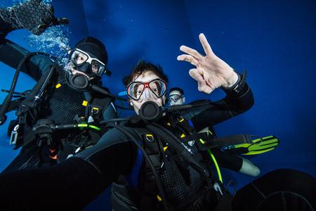 Young men scuba divers making selfie. Underwater sport and leasure activities.