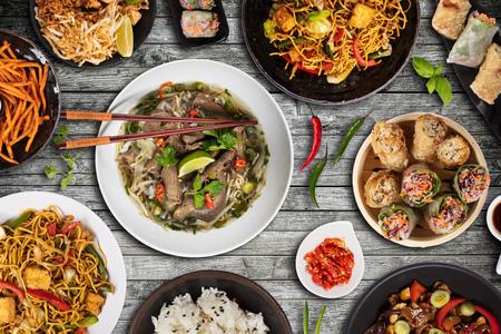 Draufsichtzusammensetzung verschiedener asiatischer Speisen in Schalen, die auf Holztisch serviert werden