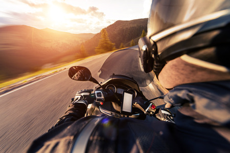 POV of motorcycle driver riding on Alpine road.