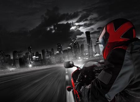 POV of super sport motorcycle driver riding towards big city. Archivio Fotografico