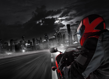 POV of super sport motorcycle driver riding towards big city.