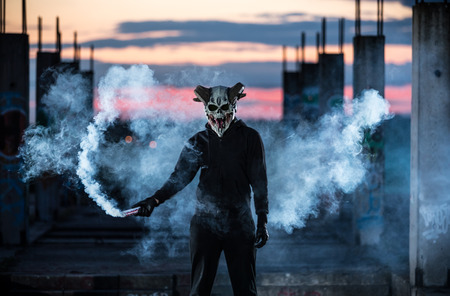 Devil with scary mask surrounded by white smoke. Halloween and horror concept