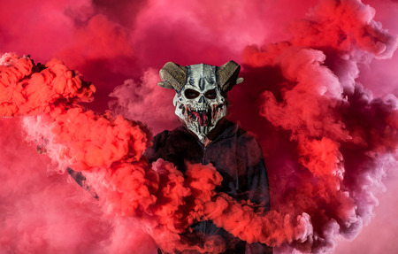 Devil with scary mask surrounded by red smoke. Halloween and horror concept