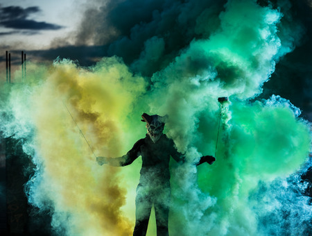 Devil with scary mask surrounded by coloured smoke. Halloween and horror concept Stock Photo - 122887334
