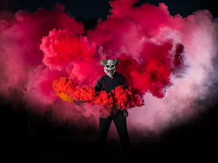 Diablo con máscara de miedo rodeado de humo rojo. Concepto de Halloween y terror
