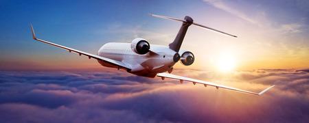 Privates Düsenflugzeug, das über Wolken im schönen Sonnenunterganglicht fliegt Modernes und schnellstes Verkehrsmittel, Geschäftsleben business