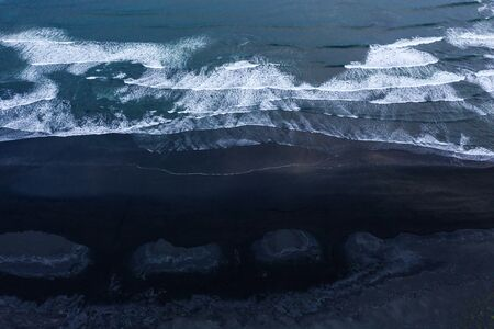 Aerial shot of black stone beach with waves, Iceland