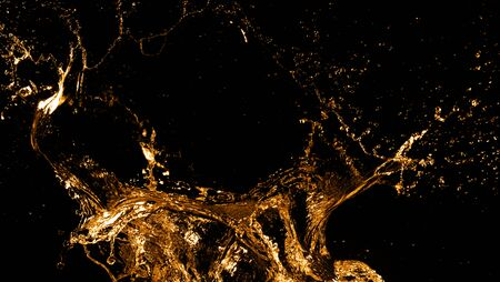 Golden splashes isolated on black background. Abstract shapes Imagens