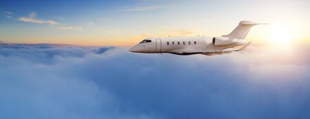 Private jet plane flying above clouds in beautiful sunset light. Modern and fastest mode of transportation, business life 스톡 콘텐츠