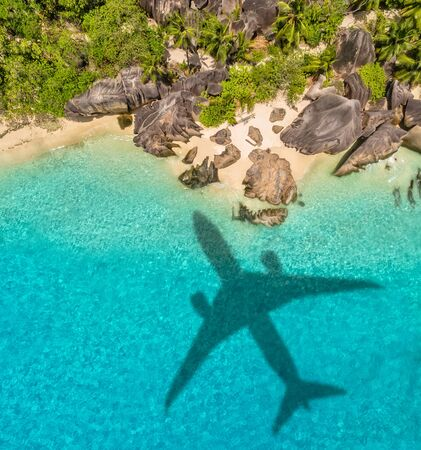 Travel concept with airplane shadow and tropical beach. Tropical paradise and beach holiday conceptual image. 스톡 콘텐츠