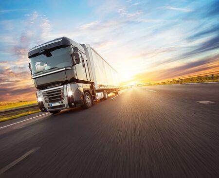 Veicolo camion europeo in autostrada con luce drammatica del tramonto. Tema di trasporto e fornitura di merci.