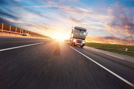 European truck vehicle on motorway with dramatic sunset light. Cargo transportation and supply theme. Banque d'images
