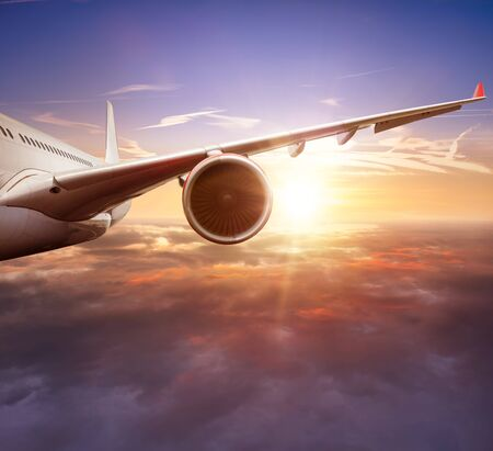 Detail of passengers commercial airplane wing flying above clouds in sunset light. Concept of fast travel, holidays and business.