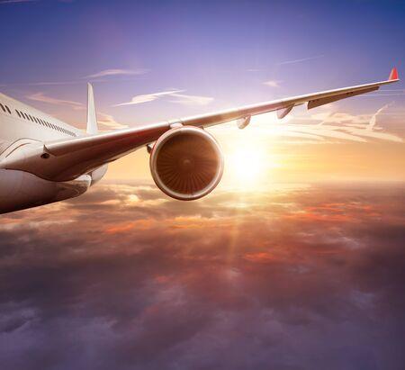 Dettaglio dell'ala di un aereo commerciale passeggeri che vola sopra le nuvole nella luce del tramonto. Concetto di viaggio veloce, vacanze e affari.