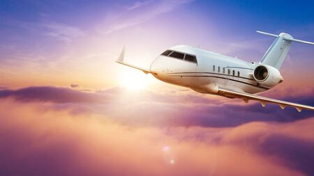 Passengers private airplane flying above clouds in sunset light. Concept of fast travel, holidays and business. 免版税图像