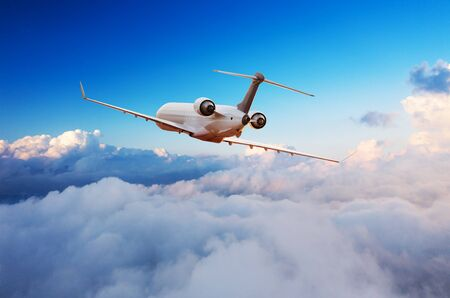 Passengers private airplane flying above clouds in sunset light. Concept of fast travel, holidays and business.