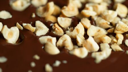 Detail of crushed hazelnuts in hot chocolate. Close-up of dark chocolate