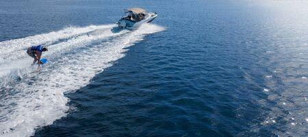 Motoscafo con pilota di wakeboard in mare aperto. Attività di svago e concetto di sport adrenalinico Archivio Fotografico