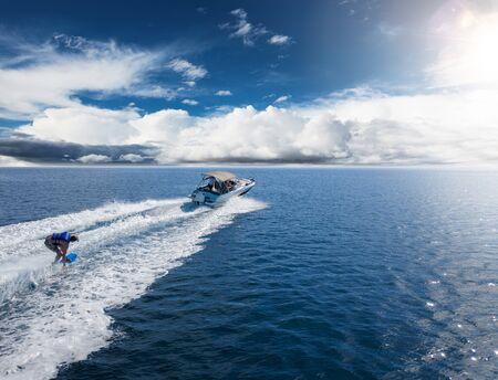 Motoscafo con pilota di wakeboard in mare aperto. Attività di svago e concetto di sport adrenalinico