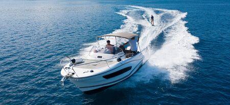 Schnellboot mit Wakeboard-Fahrer auf offener See. Freizeitaktivitäten und Adrenalinsportkonzept