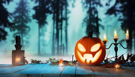 Gespenstischer Halloween-Kürbis im Wald. Gruseliger Halloween-Hintergrund mit freiem Platz für Text. Standard-Bild