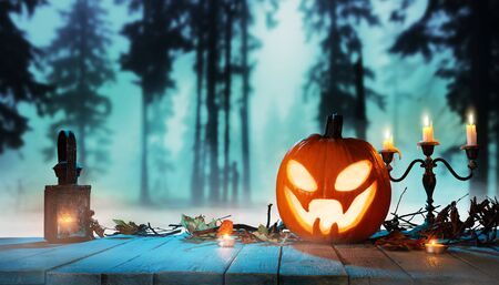 Spooky halloween pumpkin in forest. Scary halloween background with free space for text. Zdjęcie Seryjne