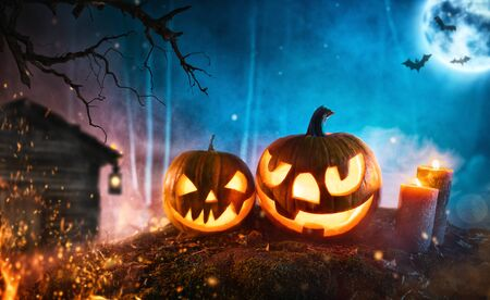 Spooky halloween pumpkins in dark mistery forest. Scary halloween background with free space for text. Zdjęcie Seryjne