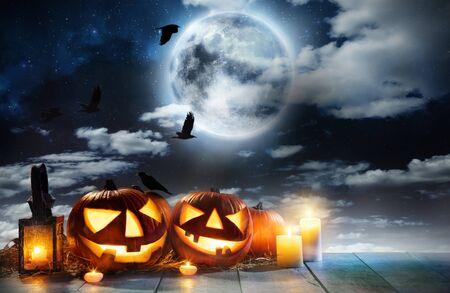 Zucca di Halloween spettrale posta su assi di legno. Sfondo spaventoso di halloween con spazio libero per il testo. Archivio Fotografico