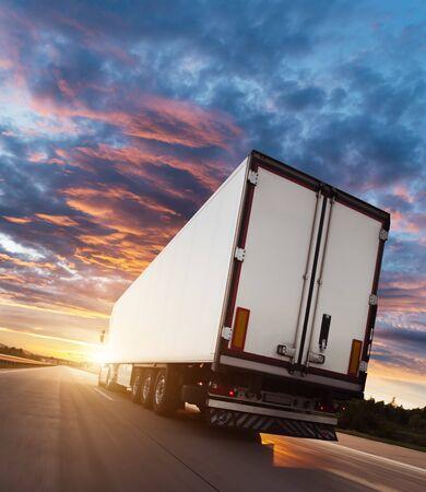 Backview del veicolo europeo del camion sull'autostrada con la luce drammatica del tramonto. Tema di trasporto e fornitura di merci.