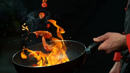 Closeup of chef holding wok pan with falling prawns with chilli peppers. Isolated on black background