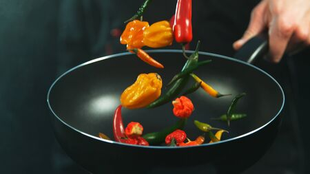 Closeup of chef holding frying with falling chilli peppers.