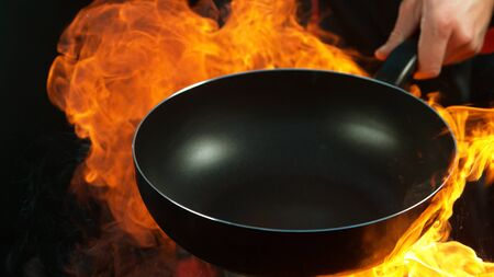 Closeup of chef holding empty wok pan with flames. Isolated on black background