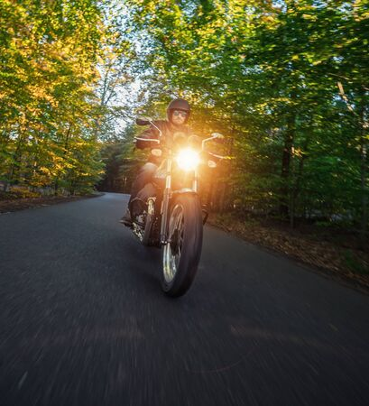 Motorcycle driver riding in foreste landscape. Lifestyle photo in sunset.