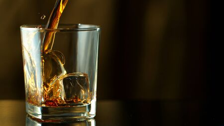 Pouring whiskey into glass in freeze motion. Free space for text, dark background. Stock fotó