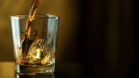 Pouring whiskey into glass in freeze motion. Free space for text, dark background.